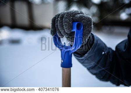 Hand In Winter Glove Holding A Handle Of A Snow Shovel, Close-up. Shoveling Snow, Winter Household C
