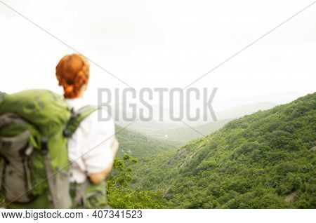 A Girl With A Green Backpack Stands And Looks At The Mountains And Forest. Travel Concept, Different