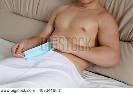 Muscular Man With Naked Torso Lying With Removed Medical Mask In Bed. Concept Of Safety Sex During C