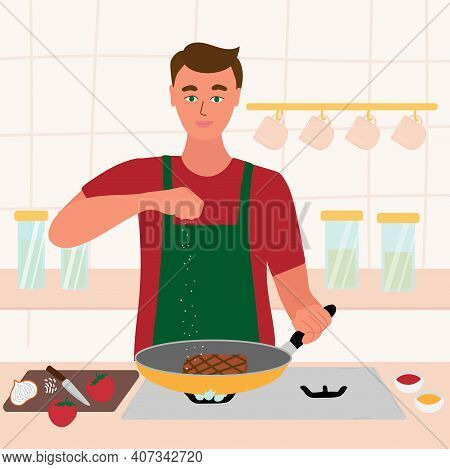 Man Cooking In His Kitchen. Male In A Red Shirt And Green Apron Roasting A Steak In A Frying Pan. Sa