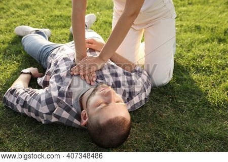 Woman Doing Cardiac Massage To Unconscious Man With Heart Attack On Green Lawn