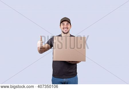 Portrait Of Happy Delivery Man Holding A Box Package And Showing Thumbs Up. Delivery Man With A Parc
