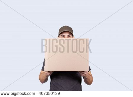 Happy Delivery Man Holding A Box Package Over Grey Background. Courier Delivering Package Express De