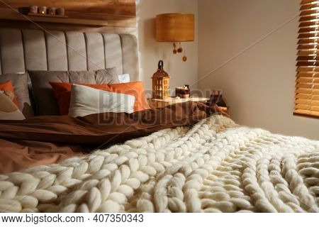 Bed With Knitted Blanket And Cushions In Room. Interior Design