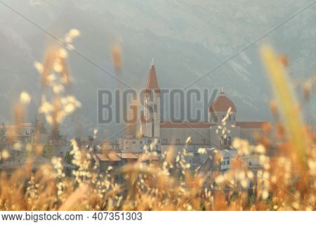 A View Of Saint Saba Church In The Lebanese Town Of Bcharre Through Yellow Grass.