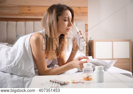 Woman Taking Medicine For Hangover In Bed At Home