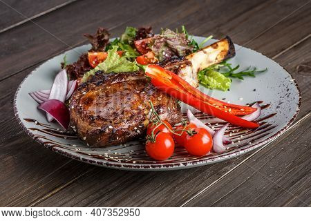 Grilled Beef Steak, Herbs And Spices On A Dark Table. Top View. Free Space For Your Text.