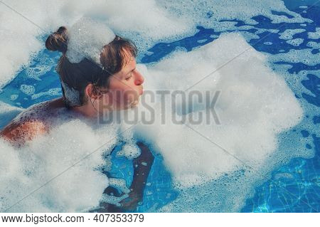 Woman Blowing On Foam Bubbles In Blue Water Pool
