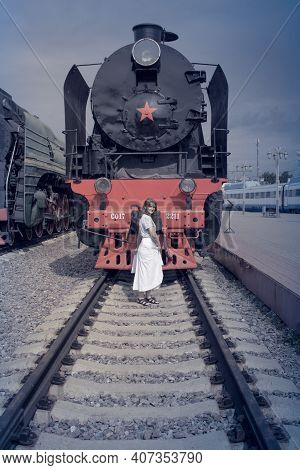 Woman Standing On The Tracks Before The Train. Dangerous Presence On The Rails. Vintage Steam Train
