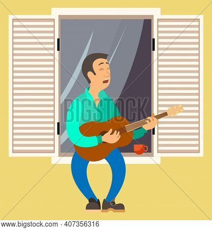 Man Is Playing The Guitar On Balcony Of His House. Musician Singing Songs And Sitting On Windowsill.