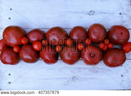 Different Varieties Of Tomatoes On A Light Background. From Cherry Tomatoes To Large Red Varieties