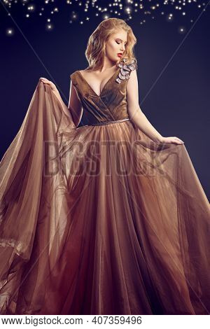 Evening dress fashion. Beautiful woman model with evening makeup and hairstyle posing in motion in a luxury evening dress on a black background.
