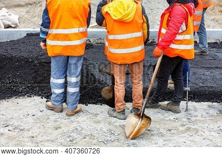 A Working Group Of Road Workers In Orange Overalls Got Together To Discuss A Work Plan For Paving Th