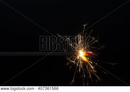 Horizontal Close-up Picture With A Burning Isolated Spark And Bright Hot Yellow Spark Flying All Dir