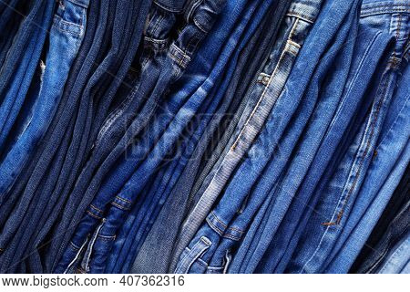 Stack or pile of denim jeans as background texture. Heap of folded jeans trousers