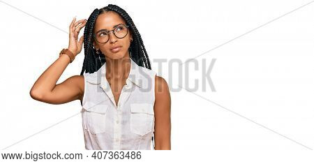 Beautiful hispanic woman wearing casual clothes and glasses confuse and wonder about question. uncertain with doubt, thinking with hand on head. pensive concept.
