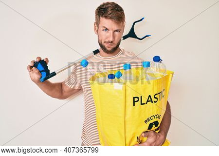 Young caucasian man holding recycling bag with plastic bottles and waste picker skeptic and nervous, frowning upset because of problem. negative person.