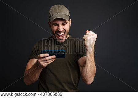 Excited masculine military man playing online game on mobile phone isolated over black background