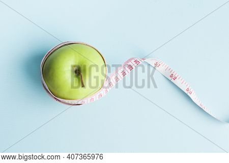 Apple With Measuring Tape On Blue Background. Weight Loss, Counting Calories And Healthy Eating Conc