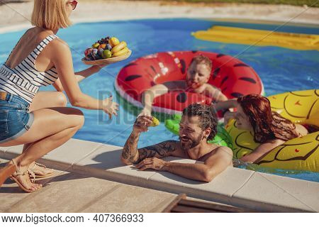 Beautiful Young Woman Bringing A Fruit Plate As A Refreshment To Her Friends While Spending Hot Sunn