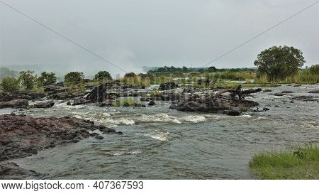 Before Falling Into The Abyss, The Zambezi River Seethes And Foams. Stones, Dry Branches Of Trees Ar