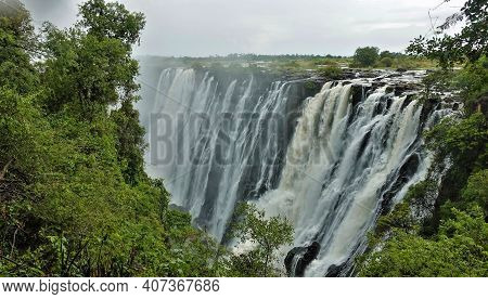 The Powerful Streams Of Victoria Falls Plunge Into The Abyss. The Rocky Channel Of The Zambezi River
