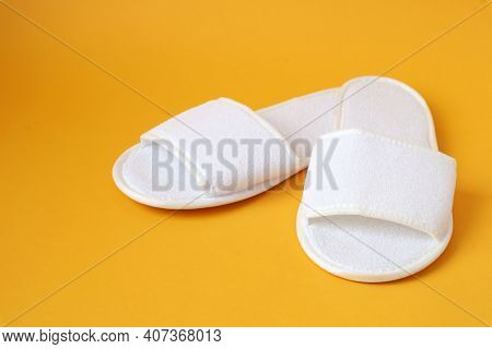 White Soft Indoor Slippers On A Yellow Background, Close-up-the Concept Of A Pleasant Stay In Sanato