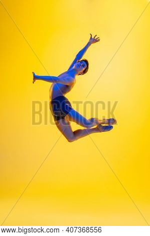 Artwork. Young And Graceful Ballet Dancer On Yellow Studio Background In Neon Light. Art, Motion, Ac