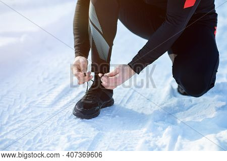Jogging In Winter. Cropped View Of Senior Man Tying Laces On His Sports Shoes On Snowy Road, Copy Sp