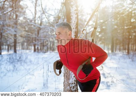 Strong Mature Man Doing Fitness Workout At Snowy Winter Park. Senior Man Engaged In Suspension Weigh