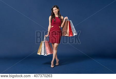 Happy Young Asian Woman Wearing Red Dress Carrying Multi Color Shopping Bags On Blue Color Backgroun