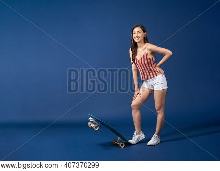 Happy Young Asian Woman Standing On Surfskate Or Skateboard On Blue Color Background, Exercise And S