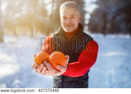 Senior Sportsman Offering Orange Fruits As Healthy Meal After Workout In Snowy Winter Park, Selectiv