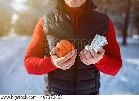 Healthy Lifestyle Vs Medical Treatment Concept. Cropped View Of Senior Sportsman Holding Orange Frui