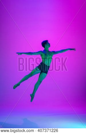 Flying. Young And Graceful Ballet Dancer On Purple Studio Background In Neon Light. Art, Motion, Act