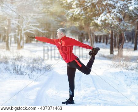 Full Length Portrait Of Mature Man In Sportswear Warming Up Before Running Outdoors On Snowy Winter
