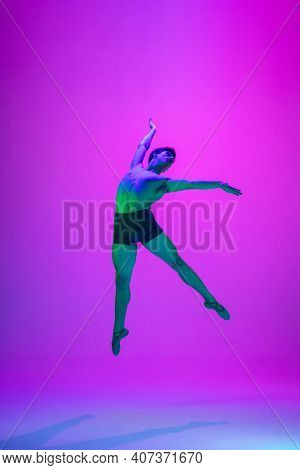 Feelings. Young And Graceful Ballet Dancer On Purple Studio Background In Neon Light. Art, Motion, A