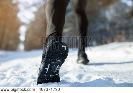 Outdoor Winter Activities Concept. Male Athlete In Sports Shoes Jogging At Park On Snowy Winter Day,