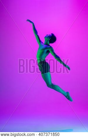 Weightless. Young And Graceful Ballet Dancer On Purple Studio Background In Neon Light. Art, Motion,