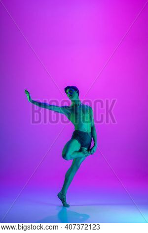Performing. Young And Graceful Ballet Dancer On Purple Studio Background In Neon Light. Art, Motion,