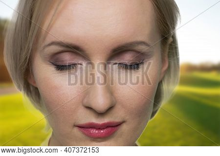 Close Up Portrait Of Womans Face. Beautiful Peaceful Woman With Closed Eyes Outdoors. Sunny Green Me
