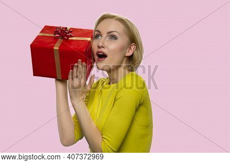 Curious Surprised European Lady With A Gift Box. Astonished Adult Woman Isolated On Pink Background.