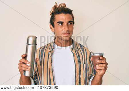 Young hispanic man drinking mate infusion smiling looking to the side and staring away thinking.