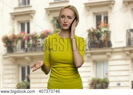 Successful Blonde Woman Is Talking On The Phone. Serious Lady In Yellow Tunic Is Having A Business C