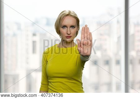 Serious Woman Is Showing Stop Gesture. Blurred Window On The Background.