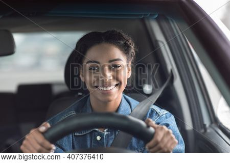 Happy Woman Driving Car And Smiling Going To Work Or On Road Trip. Cute Young Positive Happy African