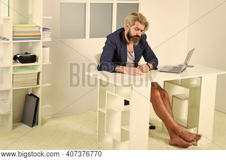 Teleworking Man In Home Office. Mature Businessman In Jacket Is Using Computer. Barefoot Man Program