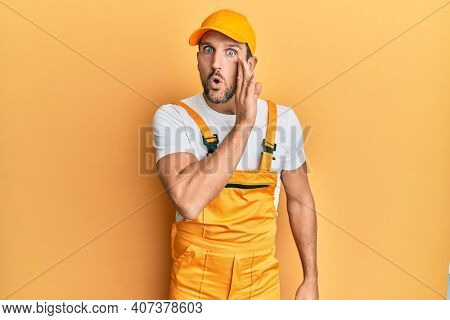 Young handsome man wearing handyman uniform over yellow background hand on mouth telling secret rumor, whispering malicious talk conversation