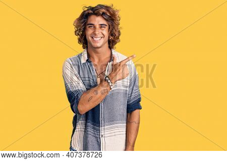 Young hispanic man wearing summer style cheerful with a smile of face pointing with hand and finger up to the side with happy and natural expression on face