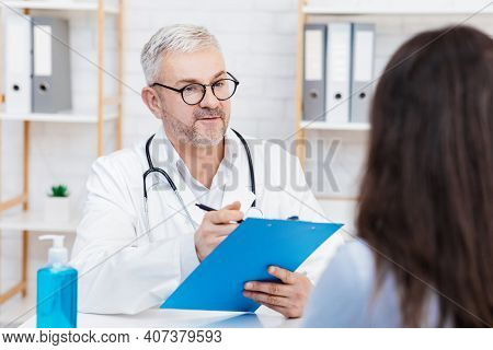Medical Professional, General Practitioner And Family Doctor. Friendly Senior Man In White Coat And